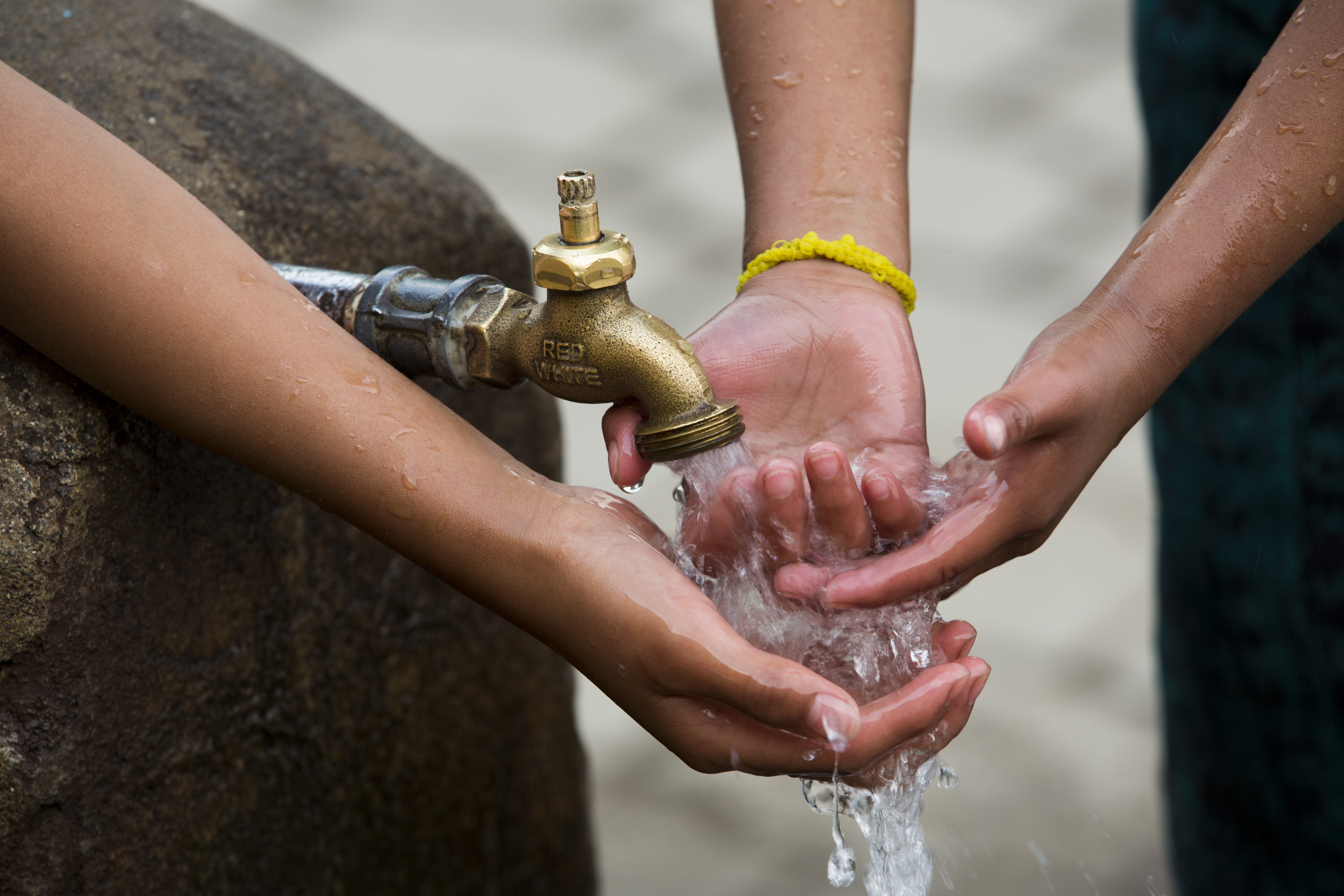 Two girls wash off their hands at a               public pila in Santa Maria, Guatemala.